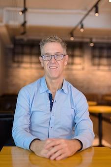 Glücklicher reifer geschäftsmann mit brillen lächelnd, während am kaffeehaus sitzend