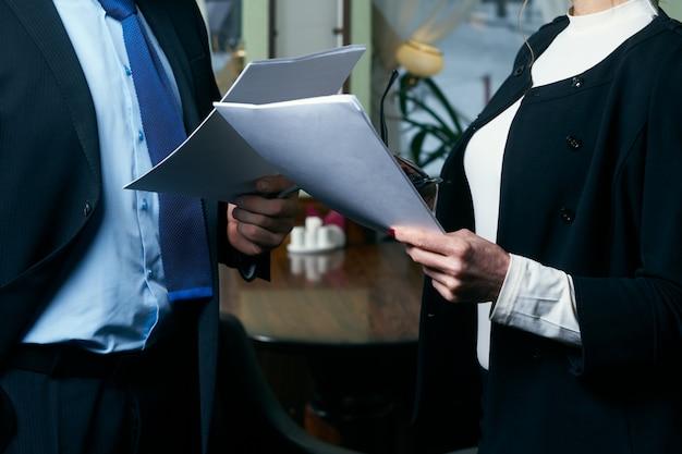 Glücklicher reifer geschäftsmann und geschäftsfrau, die mit dokumenten arbeiten