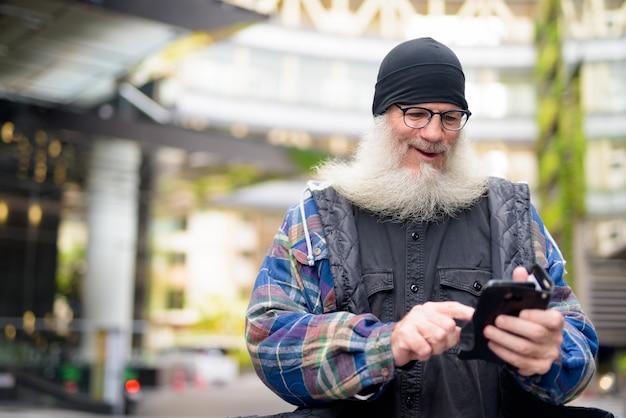 Glücklicher reifer hübscher bärtiger mann, der telefon in den straßen der stadt im freien benutzt
