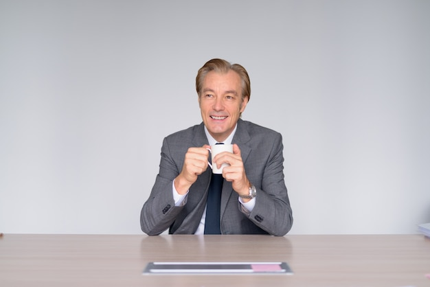 Glücklicher reifer hübscher geschäftsmann, der beim kaffeetrinken bei der arbeit denkt