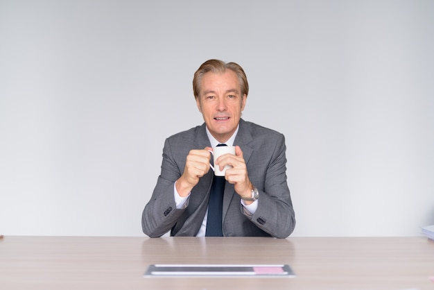 Glücklicher reifer hübscher geschäftsmann, der kaffee bei der arbeit trinkt