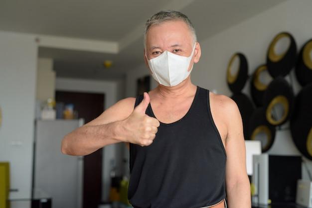 Glücklicher reifer japanischer mann mit maske, die daumen zu hause unter quarantäne aufgibt