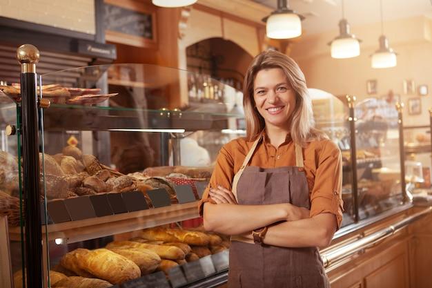 Glücklicher reifer kleiner bäckereibesitzer, der stolz an ihrem süßwarenladen lächelt