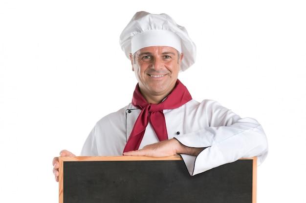 Glücklicher reifer koch, der eine leere tafel bereit für ihren text lokalisiert auf weißem hintergrund zeigt