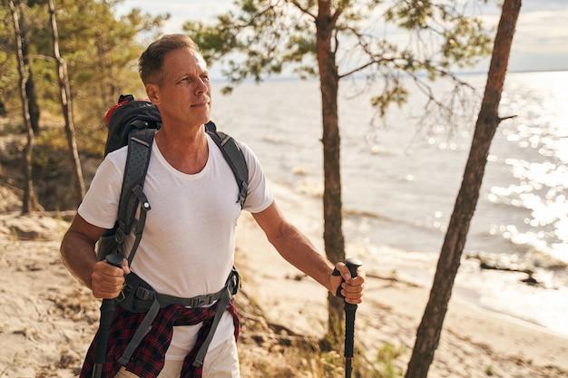 Glücklicher reifer mann geht nordic walking mit stöcken durch holz über dem meer mit rucksack