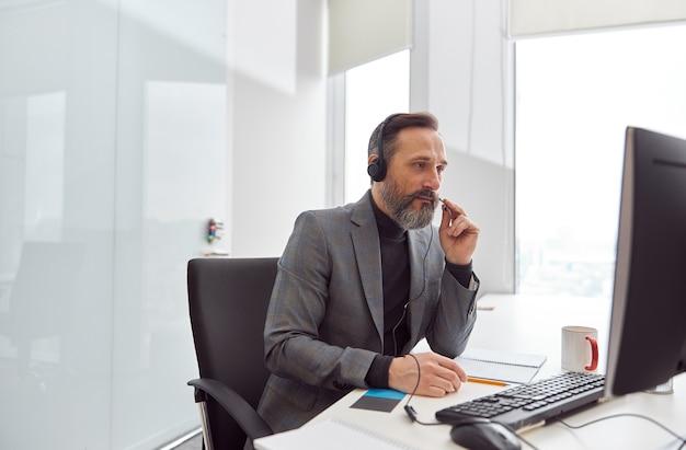Glücklicher reifer mann mit kopfhörern sitzt in einem hellweißen büro