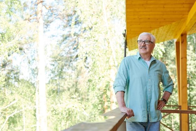 Glücklicher reifer pensionierter mann in der freizeitkleidung, die im landhaus am sommertag entspannt und natürliche umgebung betrachtet