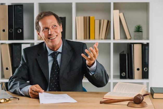 Glücklicher reifer rechtsanwalt, der im gerichtssaalgestikulieren sitzt