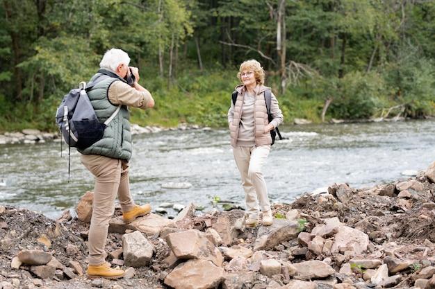 Glücklicher reifer weiblicher rucksacktourist, der am fluss vor ihrem ehemann mit kamera steht, die sie während der reise fotografiert