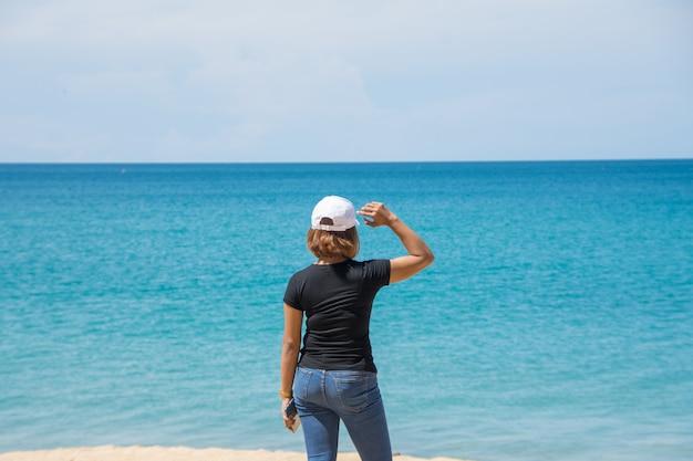Glücklicher reisefrauenstand auf sand des meeres mit blauem himmel am sonnigen tag.