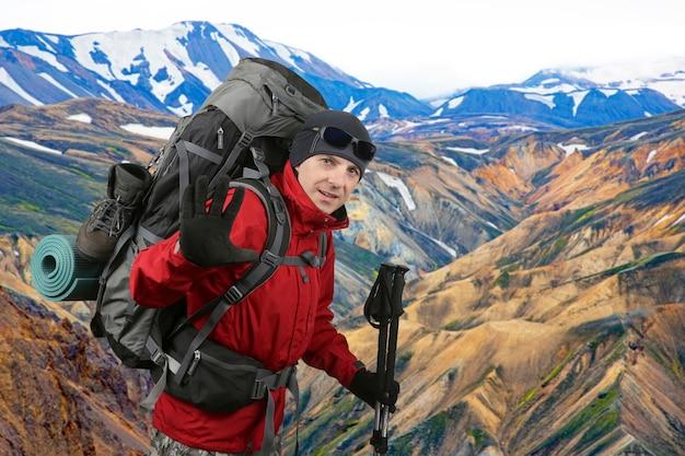 Glücklicher reisender, ausgestattet mit einer roten jacke am hang, die in der begrüßungshand erhoben wird. schöne und bunte berglandschaft in landmannalaugar, island