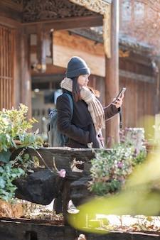 Glücklicher reisender der jungen frau, der handy- oder regalfotografie verwendet