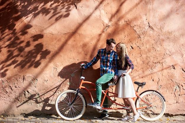 Glücklicher romantischer touristenpaar bärtiger mann und blonde frau, die zusammen auf doppeltem tandemfahrrad auf hintergrund der hohen roten alten geknisterten verputzten wand stehen.