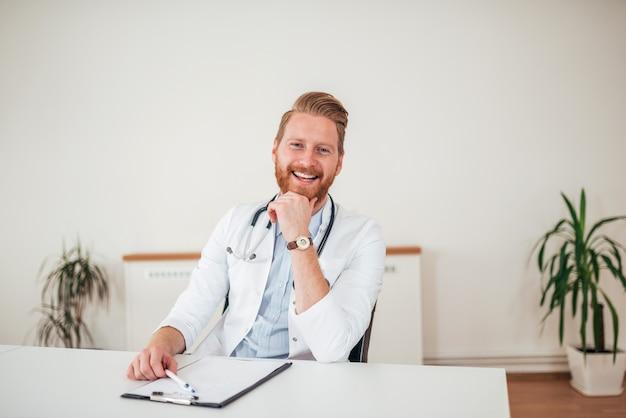 Glücklicher rothaarigedoktor am schreibtisch in der medizinischen klinik.