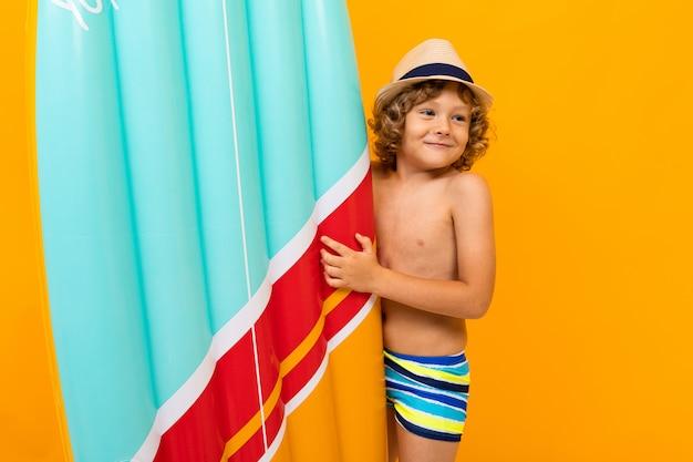 Glücklicher rothaariger junge mit einem sommerhut eine luftmatratze über gelbem hintergrund