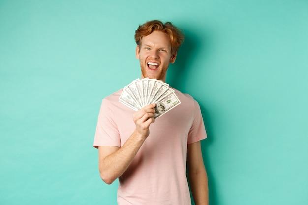 Glücklicher rothaariger mann im t-shirt, der geld in dollar zeigt und lächelt, selbstgefällige gesichter macht, nachdem er bargeld gewonnen hat, über türkisfarbenem hintergrund stehend