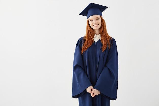 Glücklicher rothaariger weiblicher absolvent, der lächelt.