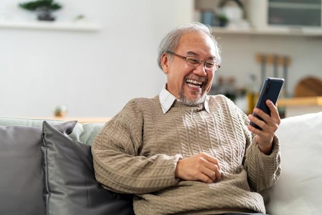 Glücklicher ruhestand älterer mann, der auf sofa mit handy sitzt