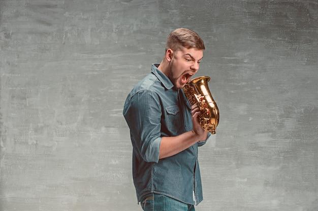 Glücklicher saxophonist, der saxophon auf grauem studio schreit