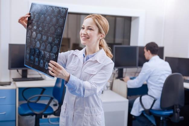 Glücklicher schöner attraktiver onkologe, der ein röntgenbild hält und es untersucht, während er nichts schlechtes sieht