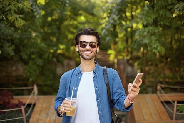 Glücklicher schöner dunkelhaariger mann in der sonnenbrille, die fröhlich schaut und handy in der hand hält, weißes t-shirt und blaues hemd tragend