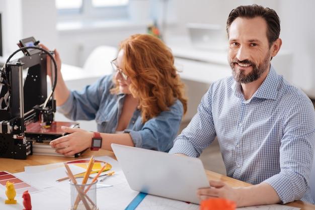 Glücklicher schöner entzückter mann, der lächelt und am laptop arbeitet, während er mit 3d-drucktechnologie arbeitet