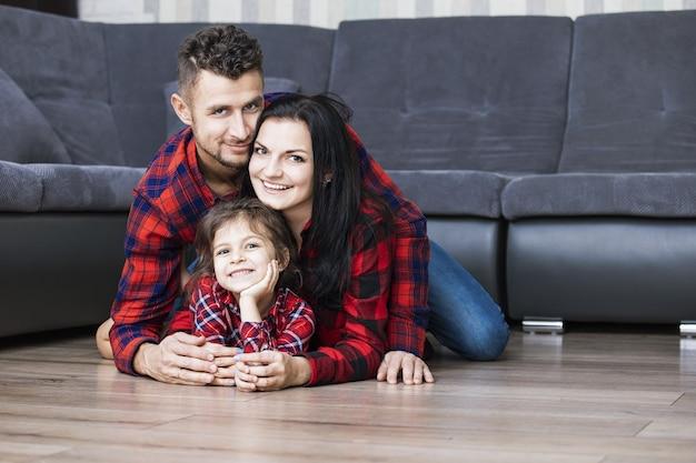 Glücklicher schöner familienvater, mutter und tochter, die zusammen zu hause lächeln, das auf dem holzboden im wohnzimmer liegt
