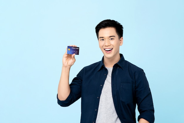Glücklicher schöner junger asiatischer mann, der kreditkarte lokalisiert zeigt
