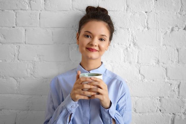 Glücklicher schöner junger frauangestellter mit rotem lippenstift und haarknoten, der drinnen aufwirft, mit ruhigem freudigem lächeln schauend, mit tasse kaffee während der pause entspannend, weißen becher in beiden händen haltend