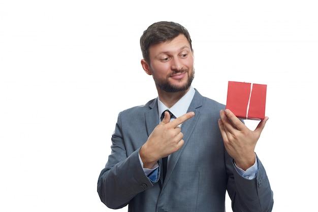 Glücklicher schöner junger mann in einem lächelnden anzug, der auf die geschenkbox zeigt