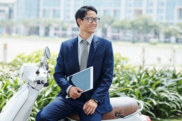 Glücklicher schöner junger vietnamesischer unternehmer mit tablet-computer, der auf roller sitzt und wegschaut
