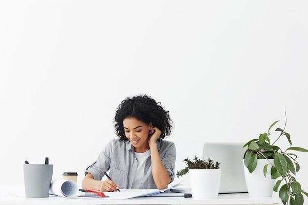Glücklicher schöner junger weiblicher architekt, der bleistift beim zeichnen von blaupausen hält