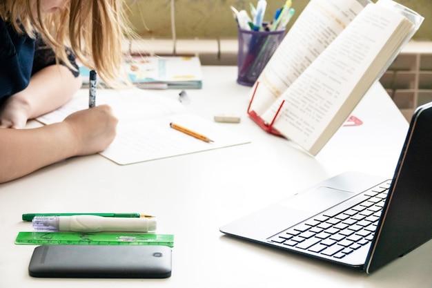 Glücklicher schöner kleiner student, der in tafelwand sitzt und mobilen pad-computer verwendet, der durch online-e-learning-system studiert.
