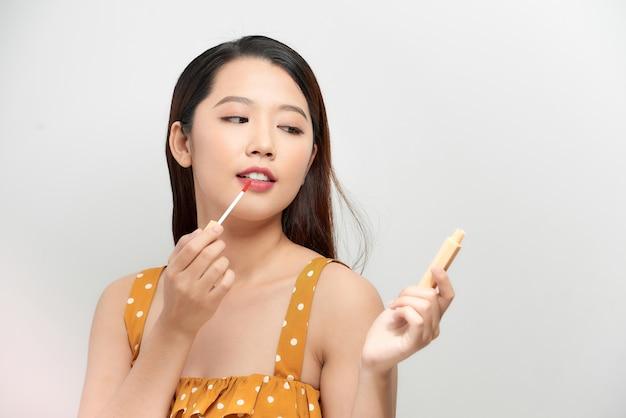Glücklicher schöner lustiger mädchengriff bilden lipglossbürsten in den händen. stylisches make-up-model