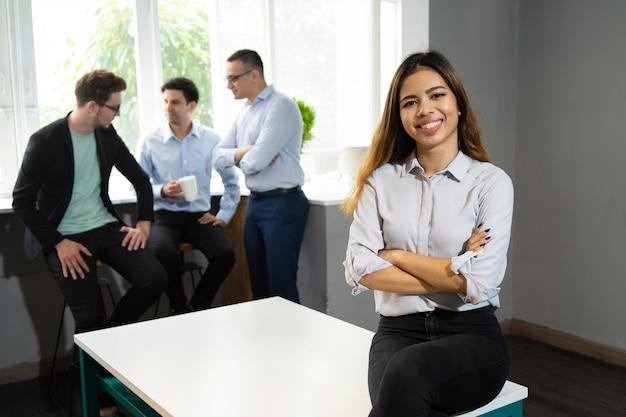 Glücklicher schöner manager, der im büroarbeitsplatz aufwirft