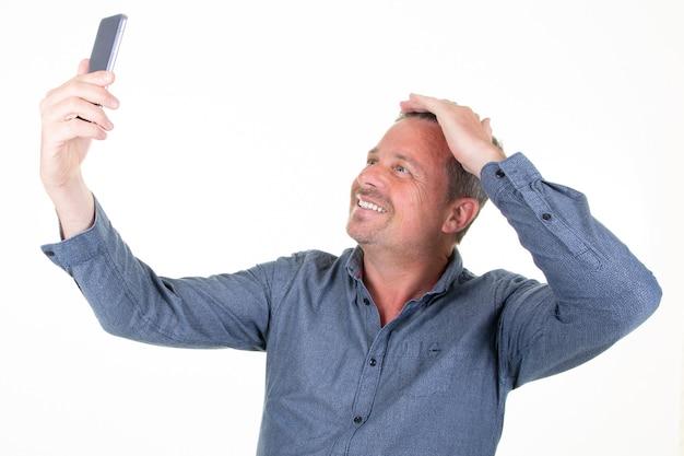 Glücklicher schöner mann, der eine selfie-fotohand auf den auf weiß lokalisierten haaren nimmt