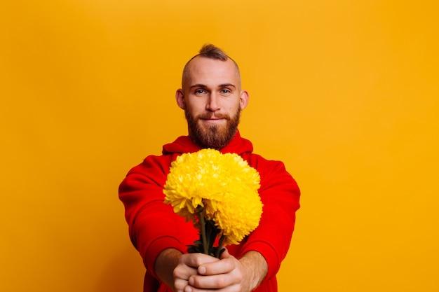 Glücklicher schöner mann mit blumenstrauß der gelben astern