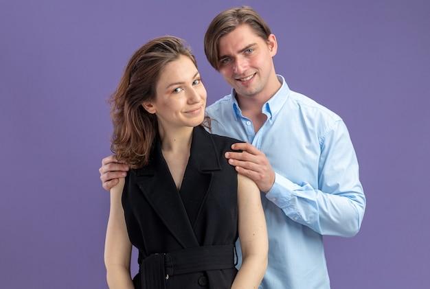 Glücklicher schöner mann und die glückliche frau des jungen schönen paares, die die kamera lächelnd betrachten, die den valentinstag über blauem hintergrund stehen