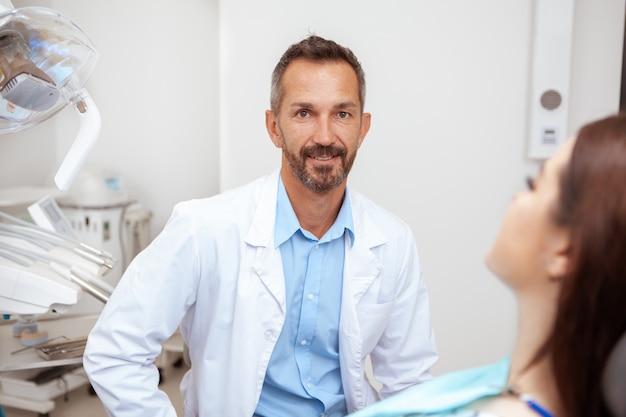 Glücklicher schöner reifer männlicher zahnarzt, der zur kamera lächelt, während er mit einem patienten an seiner klinik arbeitet