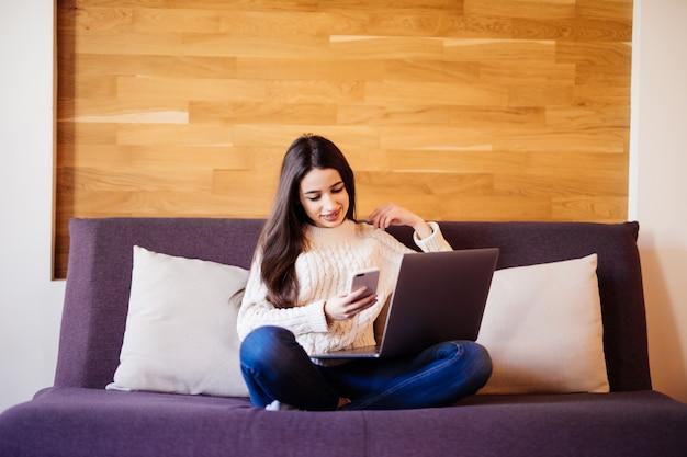 Glücklicher schöner student, der an einem laptop arbeitet, der auf dem bett im haus sitzt