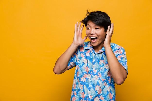 Glücklicher schreiender emotionaler junger asiatischer mann, der isoliert über gelbem raum aufwirft.