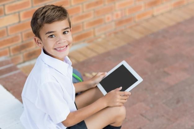 Glücklicher schüler, der im korridor sitzt und digitale tablette verwendet