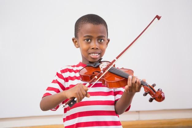 Glücklicher schüler, der violine im klassenzimmer spielt