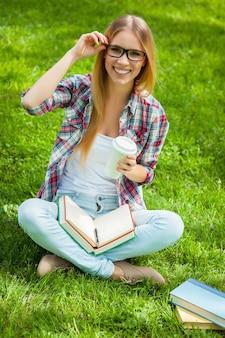 Glücklicher schüler. draufsicht einer schönen jungen studentin, die ihre brille justiert und lächelt, während sie in einem park mit büchern um sie herum sitzt?