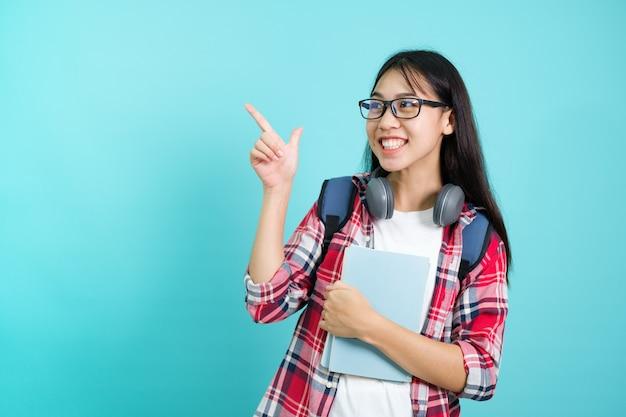 Glücklicher schüler. fröhliches asiatisches mädchen, das zur kamera lächelt, die mit rucksack im studio über blauem hintergrund steht. zurück zum schulkonzept.