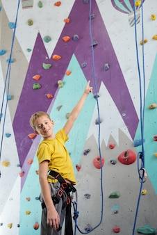 Glücklicher schüler in aktivkleidung stehend, während er vor dem training auf kletterausrüstung nach oben zeigt