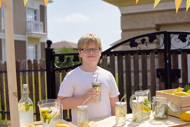 Glücklicher schuljunge mit glas der frischen kühlen limonade, die durch hölzernen stall steht und hausgemachte getränke auf hintergrund des zauns und des hauses verkauft