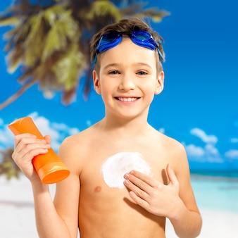 Glücklicher schulkindjunge, der sonnenschutzcreme auf den gebräunten körper anwendet. junge, der orange sonnenbräunungslotionsflasche hält.