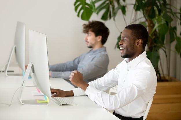 Glücklicher schwarzer angestellter, der durch on-line-gewinn oder gutes ergebnis aufgeregt wird