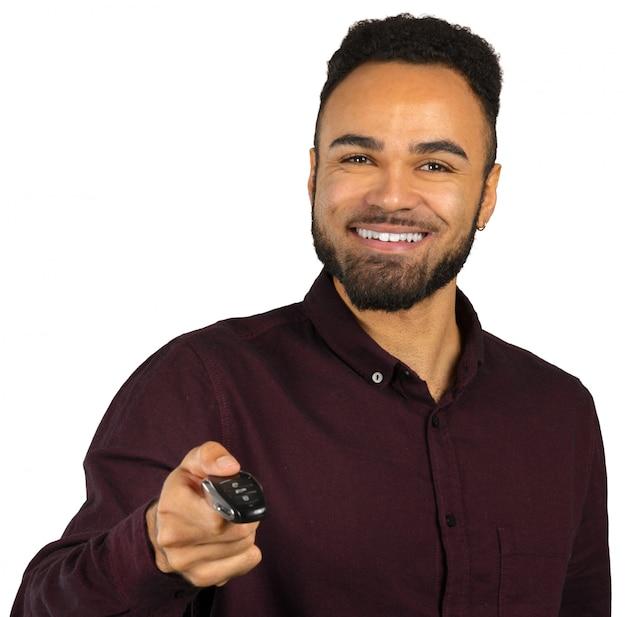 Glücklicher schwarzer junger mann, der autoschlüssel lokalisiert auf weiß hält